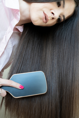 Brunette girl in a pink shirt is combing her beautiful long hair comb 免版税图像