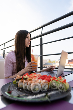 Young woman sitting in cafe at metal table, drinking juice and working on laptop.