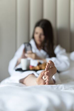 Womens legs in bed. In the background a girl with breakfast in bed Stock Photo