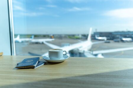 Cup of tea in airports business lounge with passports. Waiting for the flight. Airplan on the backround Stok Fotoğraf
