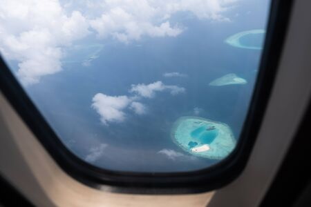 View from the porthole window on the ocean and islands of Maldives