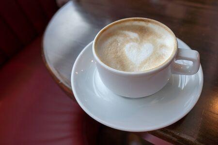 Tazza di caffè cappuccino caldo sul tavolo rosso con luce solare e ombra Rilassati e goditi il caffè