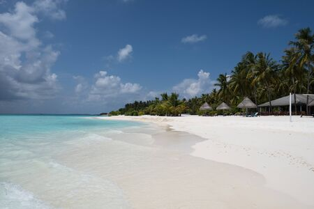 Wide sandy beach on a tropical island in Maldives