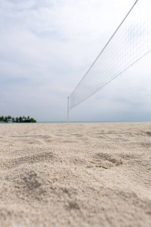 Focus on the sand in the foreground. View from a volleyball net at the beach to a tropical island in the turquoise sea