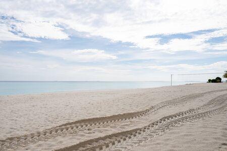 Wide sandy beach on a tropical island in Maldives. Wheel marks Stock Photo