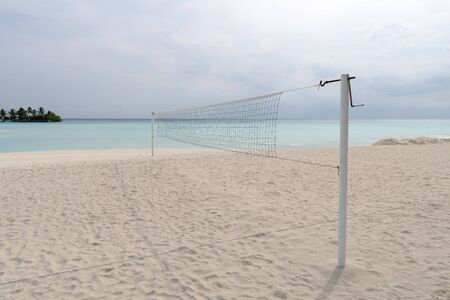 view from a volleyball net at the beach to a tropical island in the turquoise sea