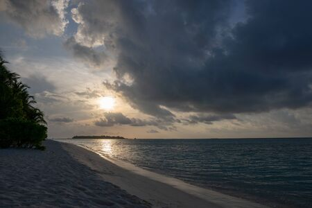 Wide sandy beach on a tropical island in Maldives on the sunset Stock Photo
