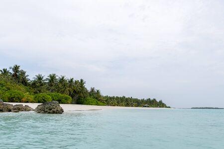 Wide sandy beach on a tropical island in Maldives