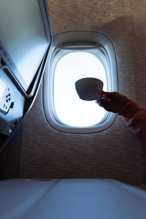 Womans hand with a coffee in airplane