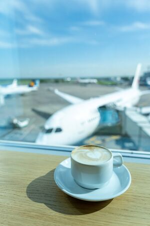 Cup of tea in airports business lounge. Waiting for the flight. Airplan on the backround