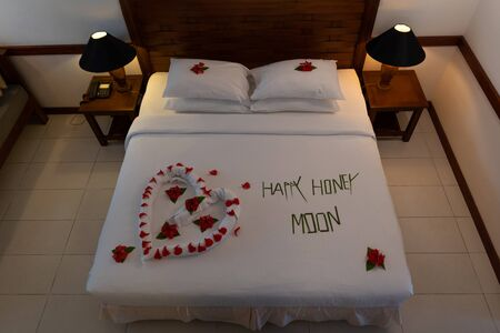 Creamy pillow and heart form, valentine signature made from red rose flower on bed decoration