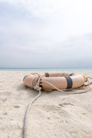 Lifebuoy and rope lie on the beach of a tropical beach.