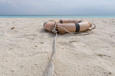 Lifebuoy and rope lie on the beach of a tropical beach