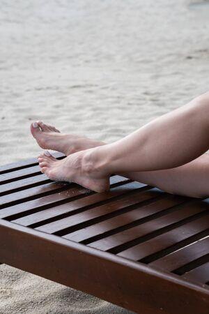 Female legs sunbathe on a lounger. Deckchair color dark wood. Stock Photo