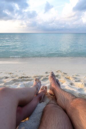 The legs of a young couple in love, who sit on the beach and see off the sunset.