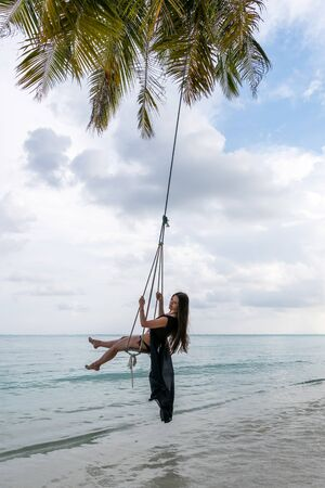 A young girl riding on a swing. Swing suspended on the palpe above the water Standard-Bild
