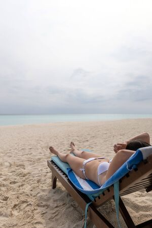 A young girl in a white bathing suit is lying on a lounger and sunbathing.
