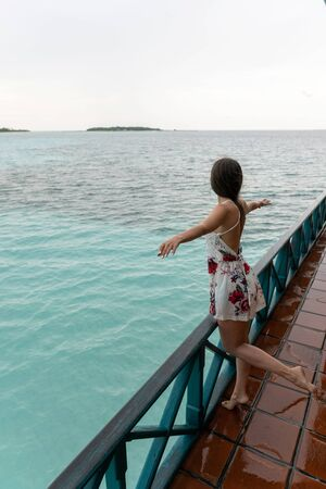 A young girl in a dress is standing in a sea restaurant. The island has rainy weather