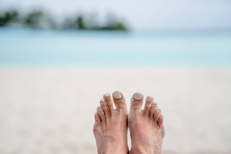 Female feet in the white sand close-up. In the background, the beach and the ocean