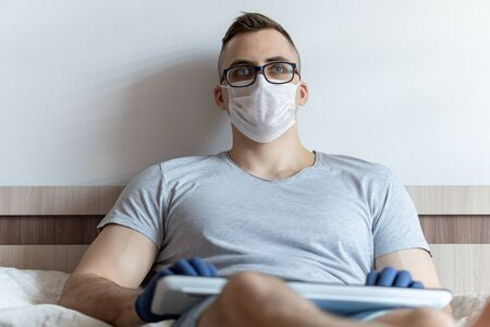 The quarantined guy works remotely from the hospital. Communication, people and freelance work concept Stock Photo