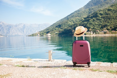 Pink suitcase with straw hat on sea beach. Concept of travel, vacation, female tourism, trip, journey, adventure. Nature background of amazing view with blue lake, coast, green mountains.