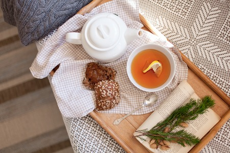 White teapot, mug of lemon tea, rye bread with seeds are serving on wooden tray on sofa. Morning breakfast, hot beverage in cozy home interior. Autumn or Christmas mood. Flat lay
