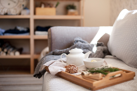 Morning at home, tea time. Wooden serving tray with white teapot, mug of hot beverage. Cozy interior in living room. Breakfast is on sofa with knitted sweater in warm light. Autumn, winter atmosphere.