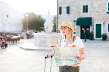 Beautiful woman traveler with city map at sunset town street. Girl tourist in hat is searching direction, sightseeing. Concept of travel, vacation, female tourism, adventure, trip, journey