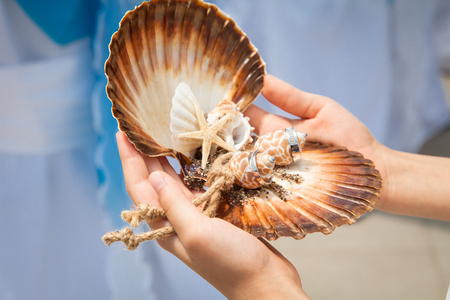 Two wedding rings on handmade ring pillow from seashells on wedding ceremony near sea outdoor. Kid girl gives silver rings to bride and groom.