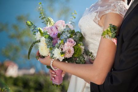 Bride and groom with wedding bouquet from roses, eucalyptus and dahlias, the bride is dressed in lace white wedding dress. 스톡 콘텐츠