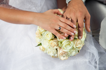 Bride and groom hold hands with golden wedding rings above wedding bouquet from white roses, cream flowers. Zdjęcie Seryjne