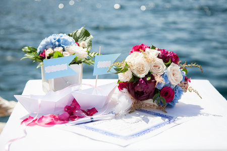 Wedding decorations for ceremony near the sea include tablets for the bride and groom names in the form of a paper boat, certificate of registration of marriage, pen, wedding bouquet from roses, peoni