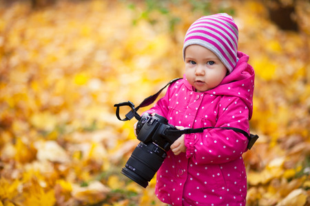 Little kid is playing with camera and taking photo of autumn nature as master. Baby is in autumn park. Girl is dressed in warm hat and jacket. Stock Photo