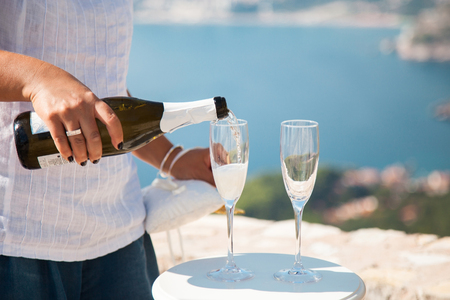 Groom as waiter pours champagne into wineglasses from bottle for guests on wedding reception before wedding ceremony. Reklamní fotografie