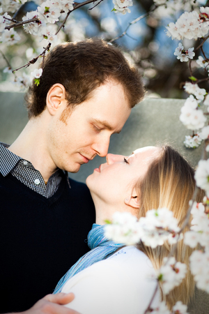 Tender couple in love under blooming cherry tree with white flowers in the park in spring. Happy girl and guy hug before kiss outdoor.