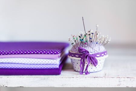 Stack of lavender and lilac fabrics and a pillow with needles for sewing, needlework, handmade on a light background. Tissues in polka dots lie on a wooden shelf in the store.