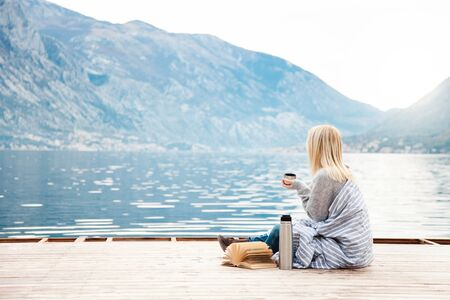 Girl on wooden pier by winter sea, mountains. Cozy picnic with hot beverages, tea, coffee or cocoa in and mug, warm plaid, opened book. Concept of enjoying nature, relaxation, reading on beach