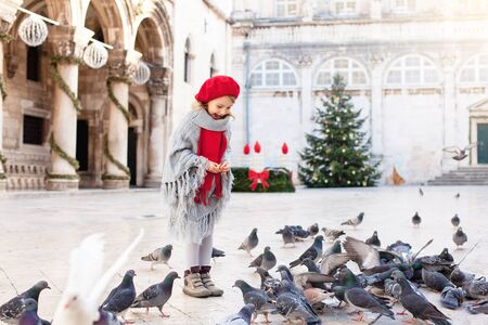 Kid girl is feeding doves on square with Christmas tree in Europe. Pigeons around cute child. Romantic vintage atmosphere on market in old town. Authentic, ancient architecture in Dubrovnik, Croatia