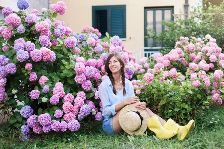 Hydrangea garden. Girl is sitting in hortensia bushes. Flower bed is pink, blue, purple and blooming in town streets by house. Young woman farmer with straw hat. Countryside life style, gardening.