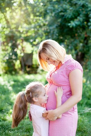 Pregnant young woman and child girl are happy, smilng and hugging. Daughter is kissing stomach of mother in sunset park. Kid is enjoying kindness and family love.