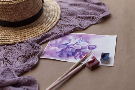 Watercolor postcard with purple flowers among brushes, paints, straw hat and knitted violet shawl. Hand drawn floral picture with lilac blooming in spring. Female leisure, hobby.