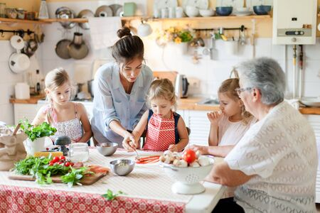 Family are cooking italian pizza together in cozy home kitchen. Cute kids, mother and grandmother are preparing food for dinner. Women are teaching three girls. Cooking class, children chef concept. Banque d'images