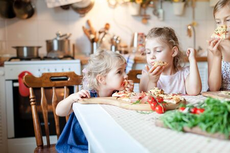 Cute hungry kids are enjoying delicious food in cozy home kitchen. Children are eating italian homemade pizza, tomatos, vegetables. Little girls at family dinner table. Lifestyle, authentic moment.