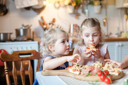 Cute hungry kids are eating italian homemade pizza in cozy home kitchen. Children are enjoying delicious food, tomatos, vegetables. Little girls at family dinner table. Lifestyle, authentic moment.