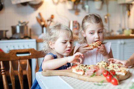Funny kids are eating, tasting italian homemade pizza in kitchen. Child is capricious, disgusted by food. Little girl dislikes, refuses and hates hot meal. Candid emotions. Lifestyle, authentic moment