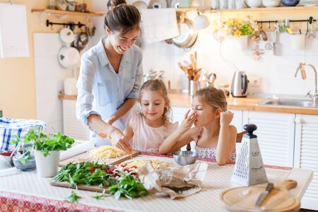 Family are cooking italian pizza together in cozy home kitchen. Cute kids with happy mother are preparing food for dinner and eating cheese. Two girls are helping woman. Lifestyle moment. 写真素材