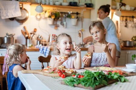 Children are eating italian homemade pizza. Cute kids are having fun while enjoying delicious food in cozy home kitchen. Three girls at family dinner table. Lifestyle, authentic moment. 写真素材