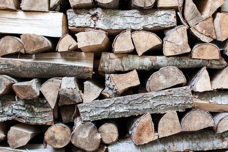 Firewood background. Pile of firewood by house. Chipped firewood is on heap. Preparation for winter. Woodpile close up.