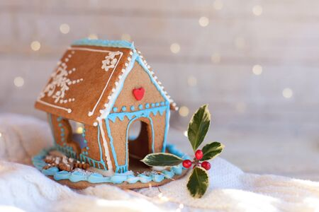 Christmas gingerbread house, decorations on wooden and knitted background with glares. Handmade sweets is decorated with green holly and cute blue, white and red ornaments, new year lights. Foto de archivo