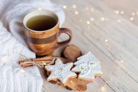 Christmas still life. Mug of tea, gingerbread cookies, cinnamon at wooden background with glares. Cozy tea time with homemade sweets and cup of hot beverage. Winter food, drink, new year lights